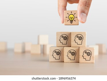 Brainstorming, creative idea or innovative idea concept. Wooden blocks with gear head icon arrangedin pyramid stairshape and a man is holding the top one with light bulb icon.