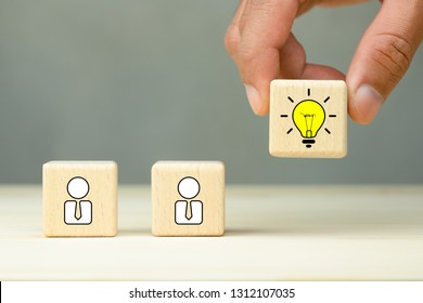 Brainstorming, Creative, New idea, innovation and solution concept. Hand picked a wooden cubes with the yellow light bulb and people icons symbol with copy space