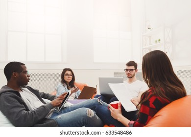 Brainstorming. Group of workers in casual clothes using gadgets, discussing affairs and smiling while working at studio