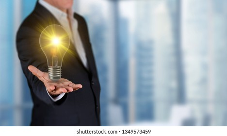 Brainstorming and inding idea concept, businessman showing 3D render glowing lighting bulb on his hand in a office. Skycrapers are in background.