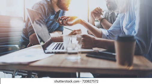Brainstorming process at sunny office.Young coworkers work together modern office studio.Young people making conversation at wooden table.Horizontal wide.Blurred background