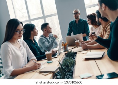 Brainstorming together. Group of young modern people in smart casual wear discussing something while working in the creative office