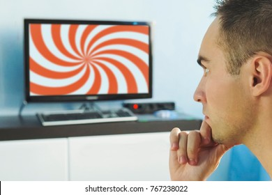 Brainwashed elderly man. hypnotic spiral on the screen of the TV. The young man hypnotized by false information on the monitor screen. False news on the Internet. viewer in front of the TV.