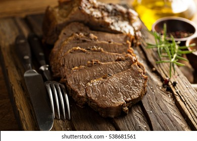 Braised beef brisket with herbs and spices on cutting board