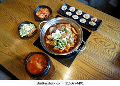 Braised chicken (Jim dak or Jjim Dak) made with cutted chicken, onion, sweet potato vermicelli, and other vegetables, marinated in a spicy soy sauce in metal hot pot on stove, Korean food recipe.