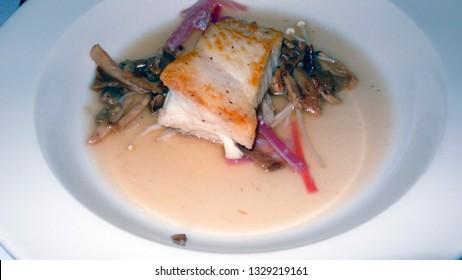 Braised halibut with wild mushrooms and mushroom nage