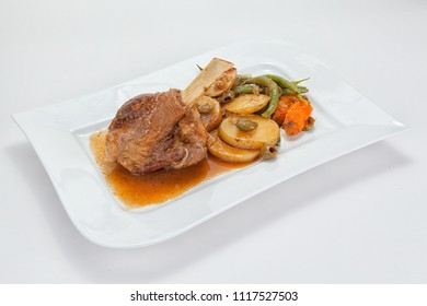 Braised lamb knuckle with vegetables on a white plate against a white background.