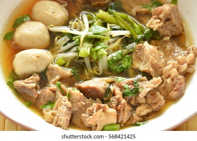 braised pork and bean sprout in brown soup on bowl