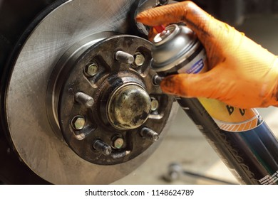 Brake cleaner being sprayed on new rotor. New brake rotor and brake pads being installed on a 2001pickup truck. Neutral color scheme. Important for safe travels. Do it yourself brake repair.