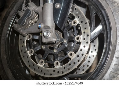 Brake disc on the front wheel of a motorcycle. Close-up.