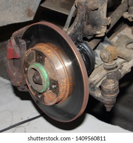 Brake disk and destroyed CV joint duster, hub and sterering rod - repair car suspension and gear drive on left side with removed wheel