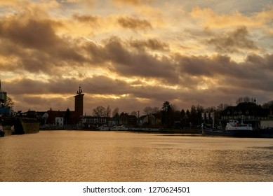 "Brake, Germany - December 30, 2018: silhouette of the tower of the church St. Marien, ships and houses in front of dramatic sunset sky at the ""Binnenhafen"" (= inner harbor)"