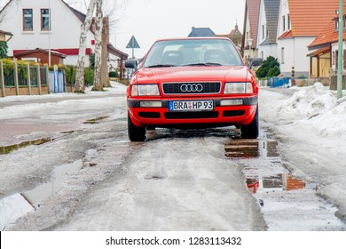 Brake, Germany - February 19, 2010: red car of the type Audi 80 B4 stands in a street that is covered with melting snow and water
