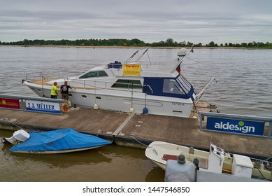 Brake, Germany - July 10, 2019: luxury yacht with advertisment for a taxi company at a pier in the river Weser on a misty day with grey sky