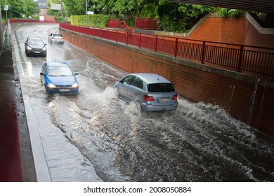 Brake, Germany - July 14, 2021: Cars drive through railroad underpass flooded by heavy rain - water splashes