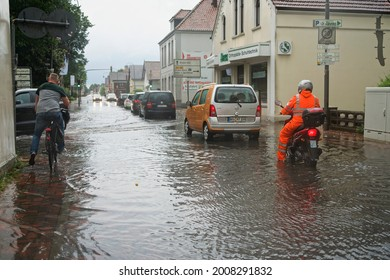 Brake, Germany - July 14, 2021: cars and a motorcycle stand in the street Kirchenstraße which has been overflooded after a heavy rainfall