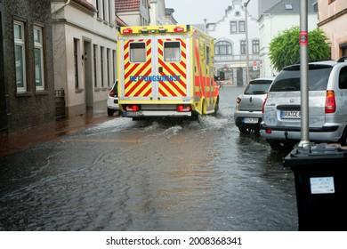 "Brake, Germany - July 14, 2021: n ambulance drives through the street ""Schulstraße"" flooded by heavy rain"