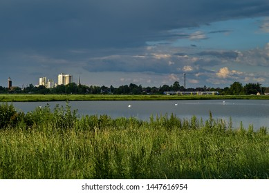 """Brake, Germany - June 13,  2019: dark raincloud over the biotope """"Kleipütte"""" in front of the skyline of the city in bright sunlight, a train of the company NordWestBahn (NWB) is passing in background"""