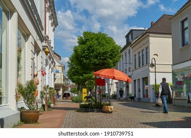 """Brake, Germany - May 29, 2020: the pedestrian zone """"Breite Straße"""" on a sunny summer day with vivid blue sky and white clouds - a colorful orange parasol is standing in front of a shop"""