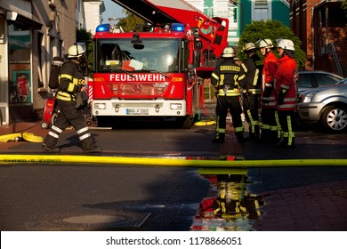 Brake, Germany - September 05, 2018: group of firefighters stands next to a fire engine while a case of emergency, one fireman with breathing apparatus crosses the street