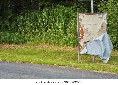 Brake, Germany - September 11, 2021: An election poster that has become detached from the wooden panel and is now hanging down with the back facing forward - underneath are remains of older posters