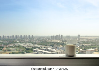 brake time with a mug of coffee and city view though window