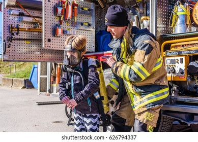 Brakne Hoby, Sweden - April 22, 2017: Documentary of public fire truck presentation. Firefighter helping young boy try a self-contained breathing apparatus.