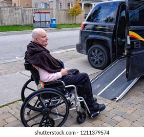 Brampton, Ontario, Canada - October 24, 2018 Senior man in wheelchair waiting to go up ramp into wheelchair cab