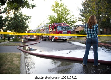 BRAMPTON, ONTARIO -  JULY 20 2012 - Teen girl stands behind police tape watching a house fire at 20 Esker Drive in Brampton Ontario on July 20, 2012