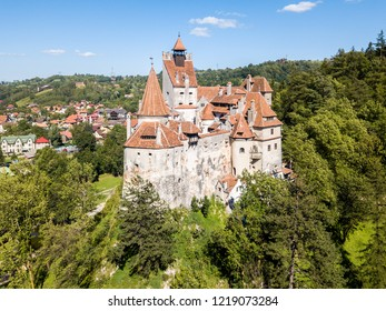 Bran castle on a hill with high spires, walls, red tiled roofs, surrounded by Bran town, Wallachia, Transylvania, Romania. Known as Drakula's Castle, after Vlad III the Impaler (Dracula, Vlad Tepes)