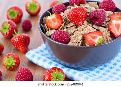 Bran flakes with fresh raspberries and strawberries on blue checkered cloth. Healthy eating choice concept
