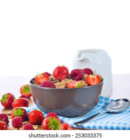 Bran flakes with fresh raspberries and strawberries on blue checkered cloth and a pitcher of milk over white background. Healthy eating choice concept