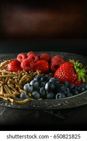 Bran flakes with fresh soft fruits with creative lighting against a dark rustic background. Generous accommodation for copy space. Concept image for healthy eating.
