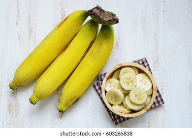 A branch of bananas and a sliced banana in a bowl