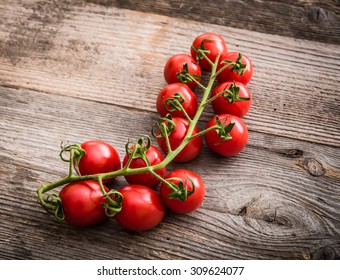 branch of cherry tomatoes on a wooden background