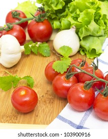 The branch of cherry tomatoes, onions, garlic, lettuce and mint on a wooden board and a towel