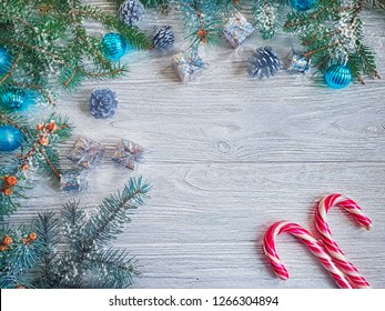 branch of a Christmas tree, a gift box, a candy on a wooden background
