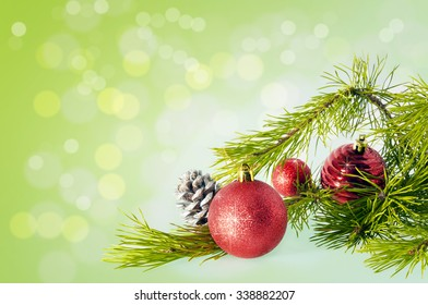 Branch Christmas tree with red balls and silver pine cones on the background bokeh with place for your text