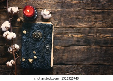 Branch of cotton tree and book of magic on a brown wooden table background with copy space.