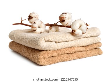 Branch of cotton and two baige cotton towels isolated on white background
