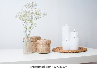 A branch of flowers in a small vase, white candles on the stand and two closed baskets on a white table in an interior