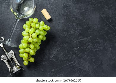 A branch of green grapes, a wine glass, a corkscrew and a cork. Concept of wine-making. Black background. Top view. Copy space