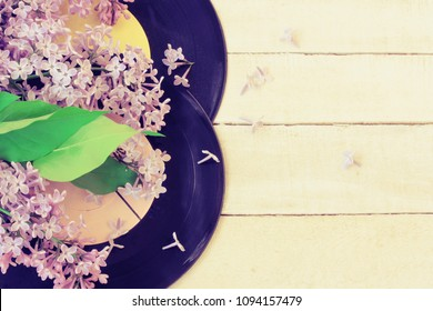 branch of lilac, two old vinyl records on wooden table, retro style music