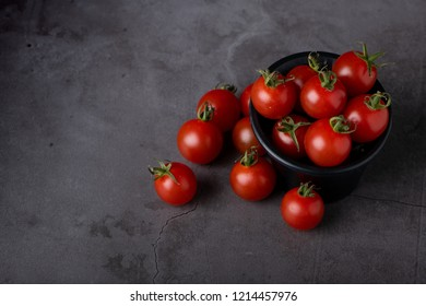 Branch of sweet tomatoes on dark background with selective focus, one of the most popular fruit in the world