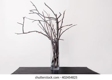 branch in the transparent vase on a wooden table and a light background