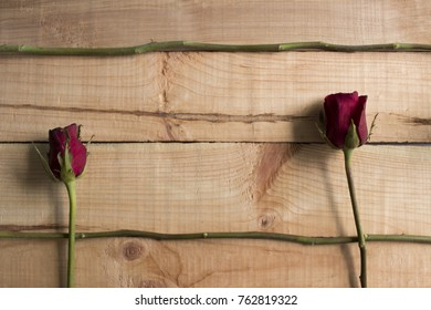 Branch and two red rose on wooden background and copyspace for use