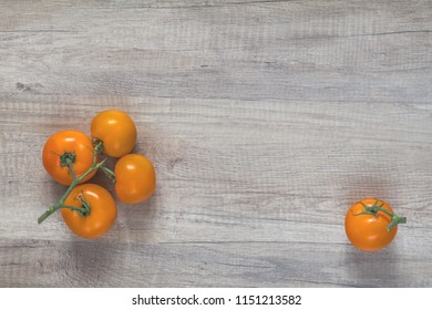 Branch yellow tomatoes on light wooden surface. Top view, copy space.
