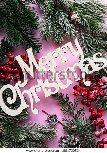 Branches of a Christmas tree and decorations on a pink pastel background with the wishes of Merry Christmas