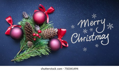"""Branches of Christmas tree on dark blue shiny background. Festive background with red Christmas balls and fir cones.  Greeting card with hand drawn letters """"Merry Christmas""""."""
