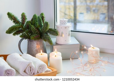 Branches of a Christmas tree in a zinc pitcher on the window. The garland is lit and the candles are burning.